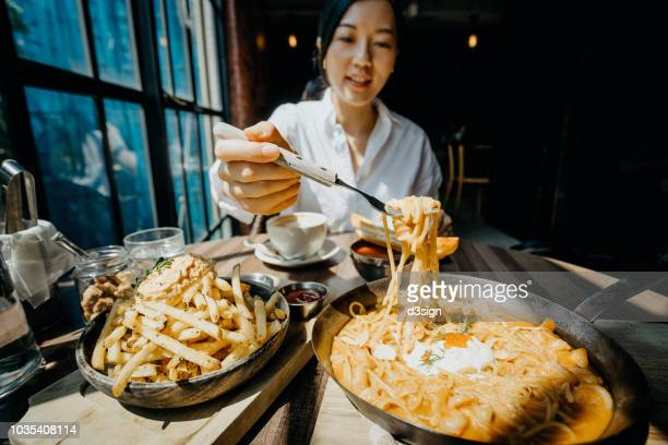 young asian woman sitting at a table by the window enjoying the warmth of sunlight and having meal joyfully in a restaurant - 不健康な食事 ストックフォトと画像