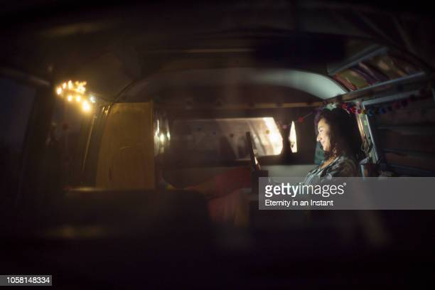 young asian woman sitting in her camper van at night - wohngebäude innenansicht stock-fotos und bilder