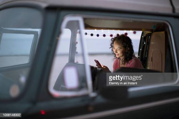 young asian woman sitting in her camper van texting - キャンプ 1人 ストックフォトと画像