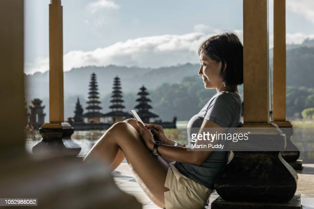 young Asian woman sitting inside pavillion using smartphone, in front of Tamblingan water temple