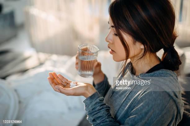 jonge aziatische vrouwenzitting op bed en het voelen ziek, dat geneesmiddelen in hand met een glas water neemt - medicijnen innemen stockfoto's en -beelden