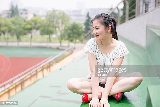 Young asian woman sitting on bleachers