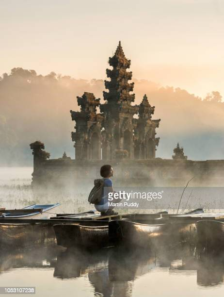 young Asian woman sitting on boat admiring Tamblingan temple