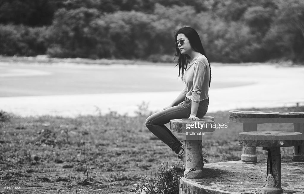 young asian woman sitting on marble chair near the beach : Stock Photo