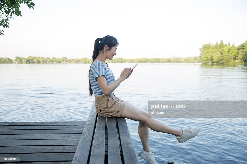 Young asian woman sitting on pier above lake,using smart phone : Foto stock
