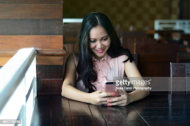 young asian woman smiling and holding a smart phone - sabah state stock pictures, royalty-free photos & images