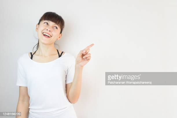 young asian woman smiling and pointing finger on copy space white background. - zeigen stock-fotos und bilder