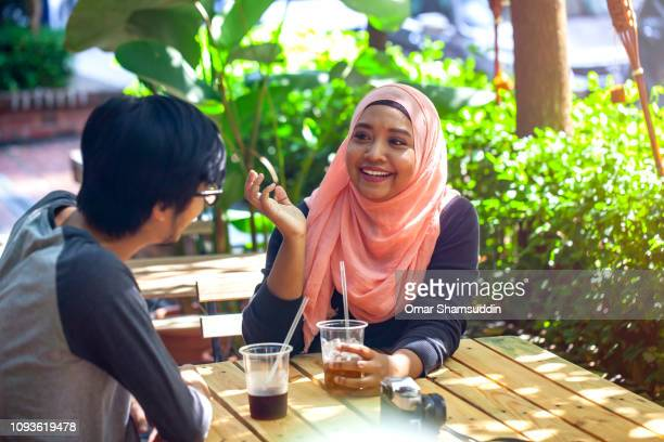 Young Asian woman spending time with friend at outdoor cafe