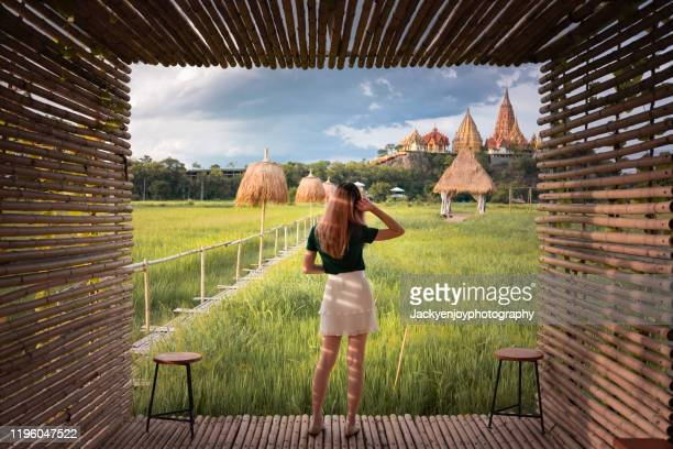 young  asian woman stand looking to wat tham suea at kanchanaburi province in thailand - カンチャナブリ県 ストックフォトと画像