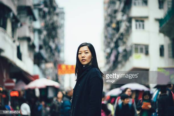 young asian woman standing against busy local city street of hong kong - busy sidewalk stock pictures, royalty-free photos & images