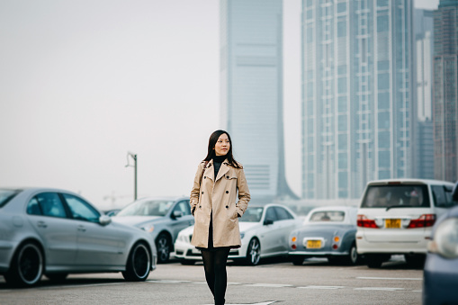 Young Asian woman standing against cityscape and looking away with confidence - gettyimageskorea