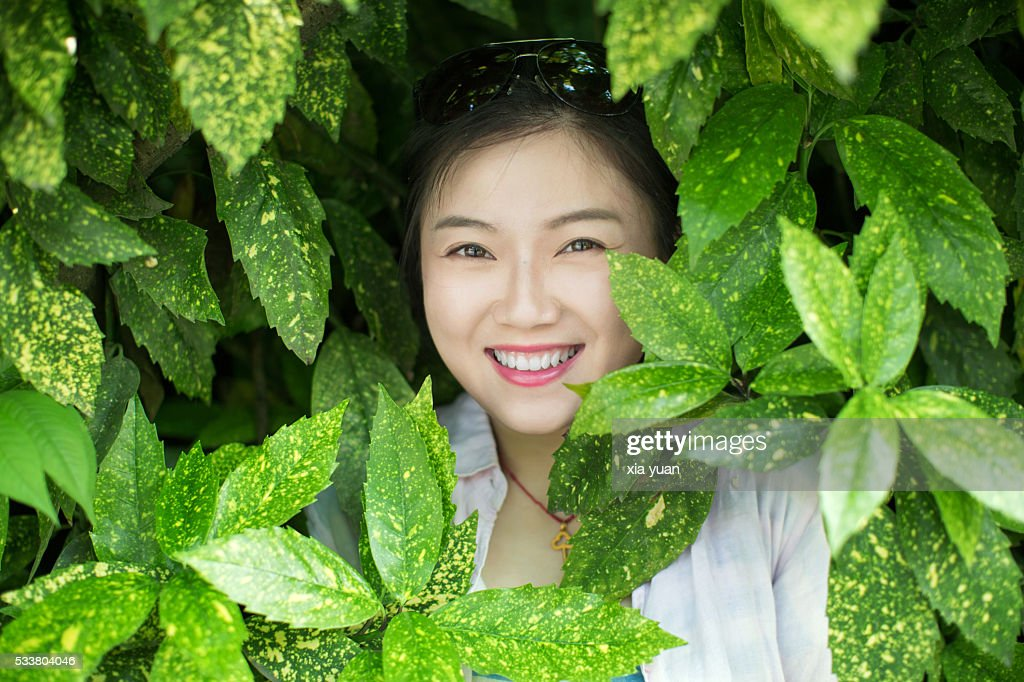 Young asian woman standing behind green leaves : Foto stock
