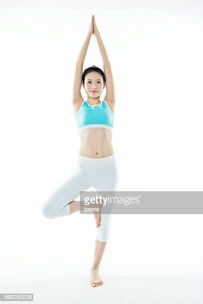 Young asian woman standing in yoga tree posture