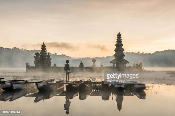 young Asian woman standing on boat admiring Tamblingan temple