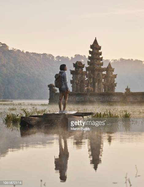 young Asian woman standing on boat admiring Tamblingan water temple