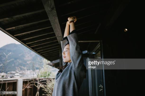 young asian woman standing on the balcony on a fresh bright morning relaxing and stretching with her eyes closed - zen like stock pictures, royalty-free photos & images