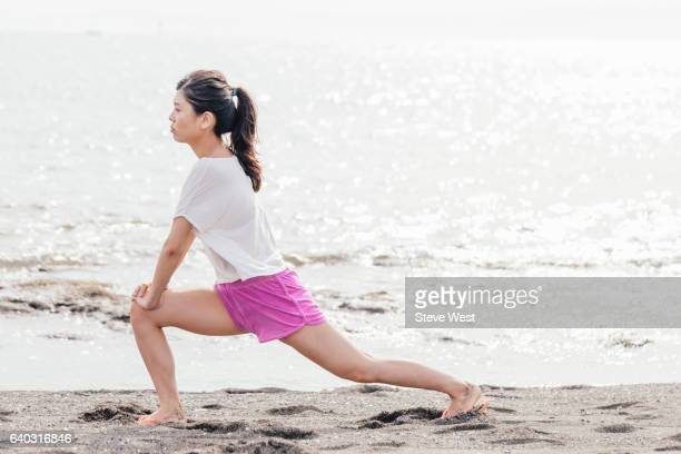 Young Asian Woman Stretching On The Beach