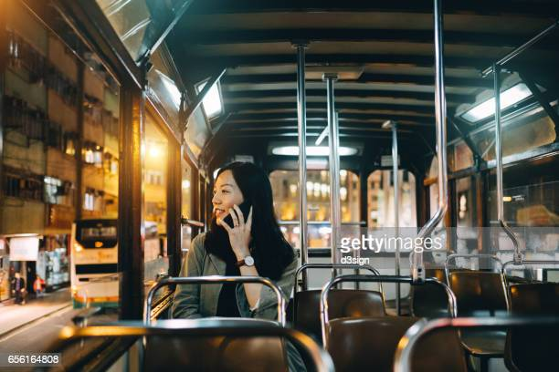 Young Asian woman talking on cell phone while looking through tram window in the evening