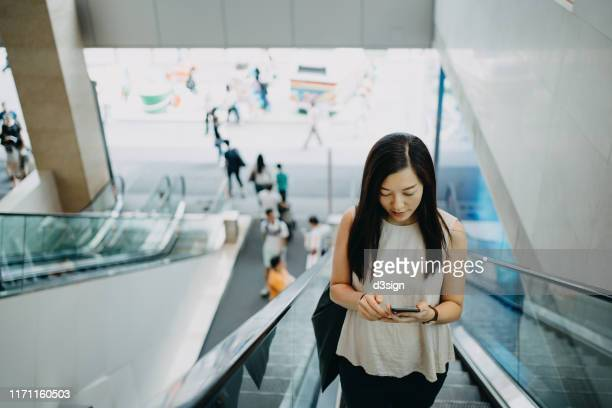 young asian woman text messaging on smartphone while riding on escalator in a building - shopping centre stock pictures, royalty-free photos & images