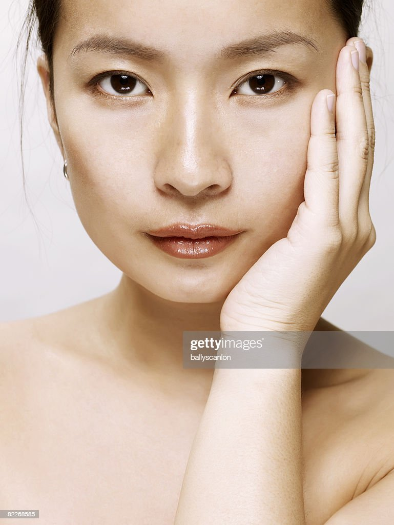 Young asian woman touching her face with her hand : Stock Photo