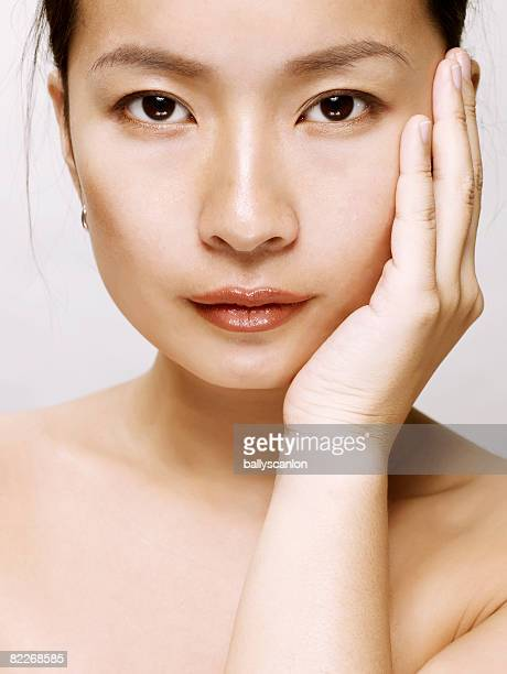 Young asian woman touching her face with her hand