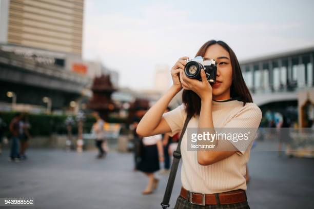 young asian woman traveler in bangkok downtown district, holding a vintage film camera - photographer stock pictures, royalty-free photos & images