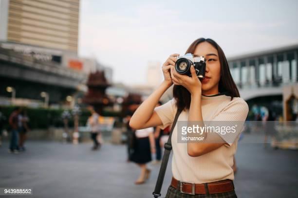 viajante da jovem mulher asiática na cidade de banguecoque, segurando uma câmera de filme vintage - temas fotográficos - fotografias e filmes do acervo