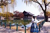 Young asian woman traveler in korean national dress hanbok in traditional dress at gyeongbokgung palace in seoul south Korea