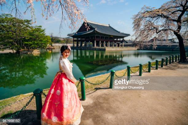 young asian woman traveler in korean national dress or hanbok traveling into the gyeongbokgung palace with cherry blossom or call sakura in spring with blue sky and clouds at seoul city, south korea. - gyeongbokgung palace 個照片及圖片檔