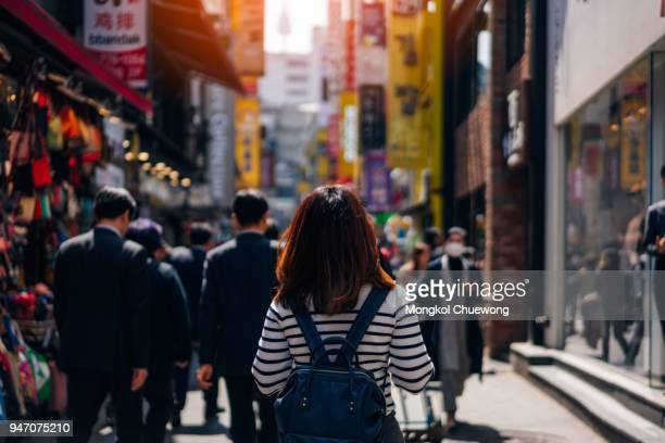 Young asian woman traveler traveling and shopping in Myeongdong street market at Seoul, South Korea. Myeong Dong district is the most popular shopping market at Seoul city.