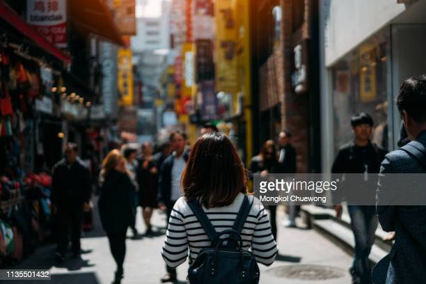 young asian woman traveler traveling and shopping in myeongdong street market - korean teen stock pictures, royalty-free photos & images