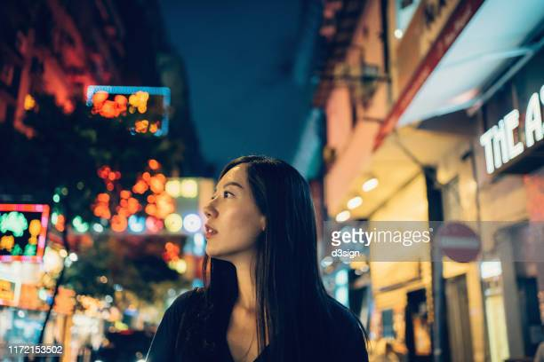 young asian woman traveller exploring along busy downtown city street at night, with multi coloured commercial signs and neon lights in the background - fashion hong kong stock photos and pictures