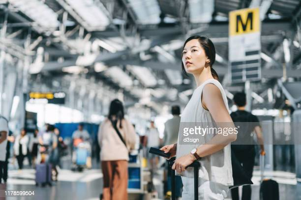 young asian woman traveller holding passport and suitcase walking in the international airport hall - passenger stock pictures, royalty-free photos & images