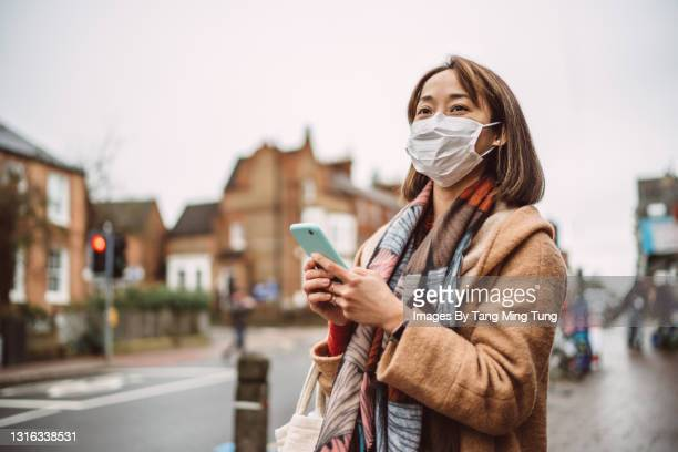 young asian woman traveller in protective face mask using gps navigation with her smartphone while exploring in town - town stock pictures, royalty-free photos & images