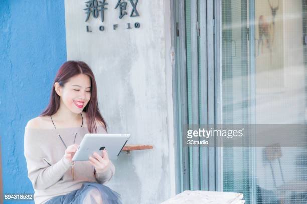 A young Asian woman uses mobile devices eg iPad Mac Book Air and iPhone for communication at one of the cafe in Central district on 15 December in...