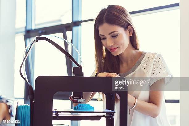 Young asian woman using 3D printer