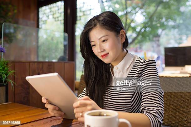 Young asian woman using a digital tablet in a cafe