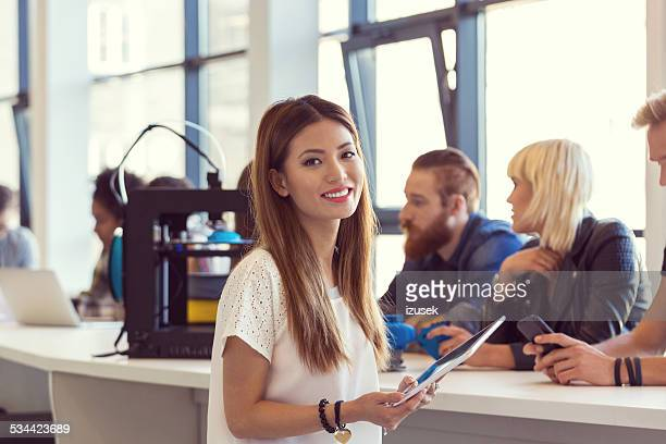 Young asian woman using digital tablet in 3D printer office