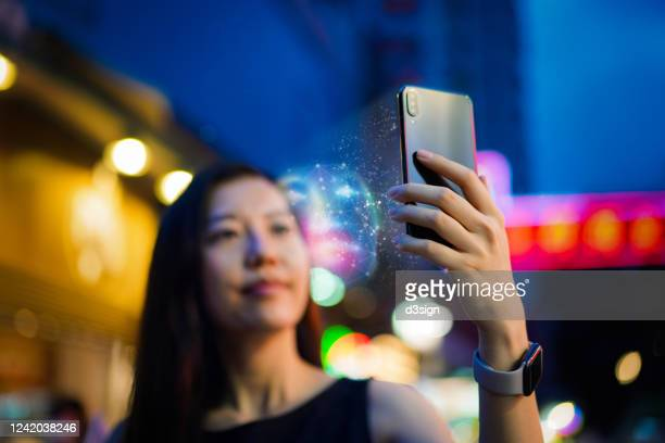 young asian woman using face recognition software via smartphone, in front of colourful neon signboards in busy downtown city street at night. biometric verification and artificial intelligence concept - identity photos et images de collection