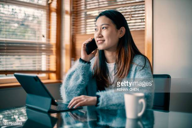 jonge aziatische vrouw die laptop gebruikt die thuis tijdens covid-19 werkt - flexplekken stockfoto's en -beelden