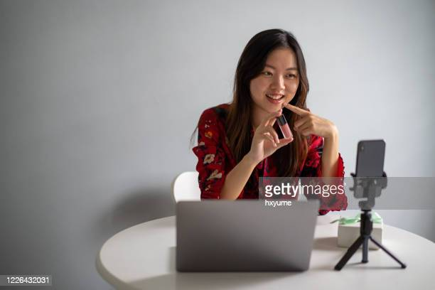 young asian woman using live social media to sell her product via smartphone - social media marketing stock pictures, royalty-free photos & images