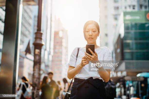 young asian woman using mobile phone while commuting in downtown hong kong, against busy commuters and urban skyscrapers - fashion hong kong stock photos and pictures