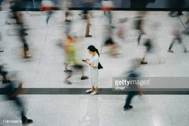 young asian woman using smartphone surrounded by commuters rushing by in subway station - urgency stock pictures, royalty-free photos & images