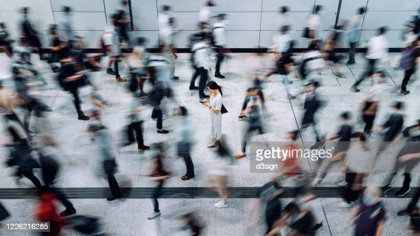 young asian woman using smartphone surrounded by commuters rushing by in subway station during office peak hours in the city - dringendheid stockfoto's en -beelden