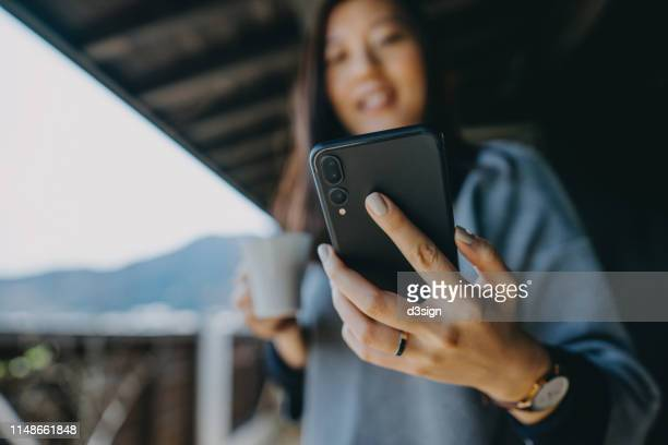 young asian woman using smartphone while relaxing with coffee in the balcony on a fresh morning - photo messaging stock pictures, royalty-free photos & images