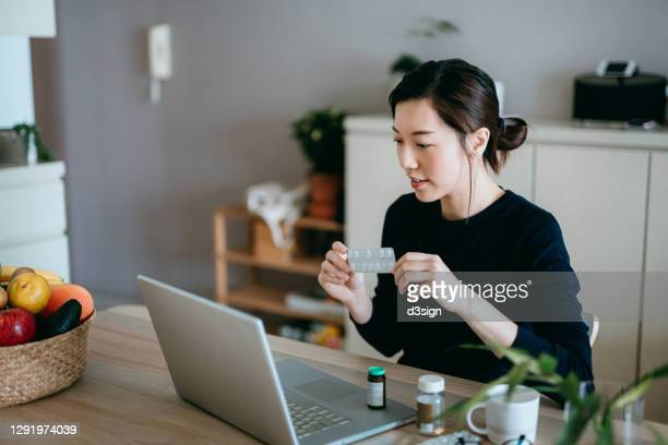 young asian woman video conferencing with laptop to connect with her family doctor, consulting about medicine during self isolation at home in covid-19 health crisis - healthcare stock pictures, royalty-free photos & images