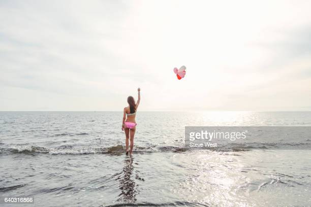 Young Asian Woman Walking In The Ocean Holding Balloons