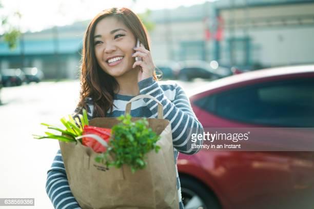 Young Asian woman walking through a parking lot holding a shopping bag
