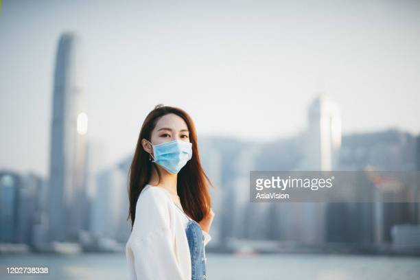 young asian woman wearing a protective face mask to prevent the spread of coronavirus, a global health emergency over outbreak - infectious disease stock pictures, royalty-free photos & images