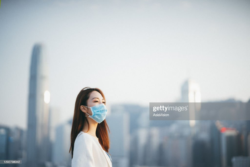 Young Asian woman wearing a protective face mask to prevent the spread of coronavirus, a global health emergency over outbreak : Stock Photo